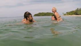 Os povos felizes que têm a natação do divertimento na câmera pov da ação do mar de amigos brincalhão novos agrupam junto na praia vídeos de arquivo