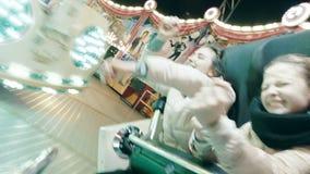 Os povos felizes têm o divertimento na atração no parque de diversões na noite As jovens mulheres obtêm emoções afiadas da elevaç filme