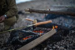 Os povos fritam salsichas em um fogo aberto fotografia de stock