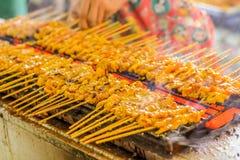 Os povos grelharam satays da carne de porco no forno do fogão Fotos de Stock Royalty Free