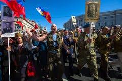 Os povos guardam bandeiras e imagens de soldados da segunda guerra mundial enquanto participam no março imortal do regimento Imagem de Stock Royalty Free