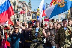 Os povos guardam bandeiras e imagens de soldados da segunda guerra mundial enquanto participam no março imortal do regimento Fotografia de Stock Royalty Free