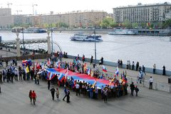 Os povos guardam uma bandeira do russo e estão pelo rio de Moscou. Imagem de Stock
