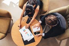 Os povos incorporados que discutem o negócio novo projetam-se usando cartas Imagem de Stock