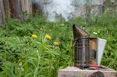 Os povos inflamam o dispositivo para fumigar as abelhas com fumo fotografia de stock royalty free