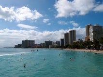 Os povos jogam na água protegida e penduram para fora na praia dentro fotografia de stock royalty free