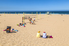 Os povos jogam o voleibol e treinam-no na praia Fotos de Stock