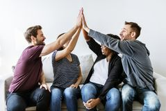 Os povos juntados entregam junto no sofá Foto de Stock