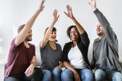 Os povos juntados entregarem junto quando no sofá Fotos de Stock