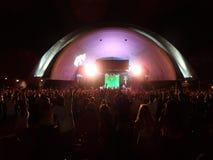 Os povos levantam as mãos no ar durante o concerto de SOJA Imagem de Stock