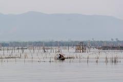 Os povos mantêm o equipamento de pesca no barco Foto de Stock