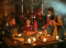 Os povos medievais comem e bebem na taberna do castelo Foto de Stock Royalty Free