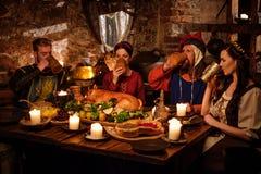 Os povos medievais comem e bebem no interior antigo da cozinha do castelo Fotos de Stock Royalty Free
