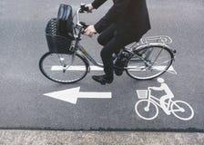 Os povos montam a bicicleta no Signage da pista da bicicleta da estrada foto de stock