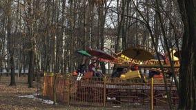Os povos montam no passeio do arco-íris no parque de diversões na primavera em BOBRUISK, BIELORRÚSSIA 03 09 19 Os povos felizes g vídeos de arquivo