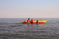 Os povos montam o mar em uma banana inflável fotos de stock