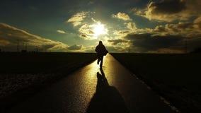 Os povos mostram em silhueta na estrada na natureza do campo na paisagem do por do sol filme