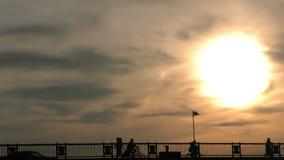 Os povos mostram em silhueta a passagem na ponte e no por do sol filme
