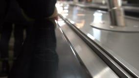 Os povos movem-se em uma escada rolante, mão humana nos trilhos filme