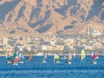 Os povos movem-se nos barcos com uma vela e um windsurfe no Mar Vermelho Fundo - as montanhas e a cidade de Aqaba foto de stock
