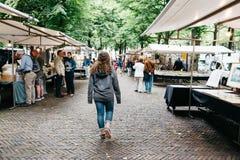 Os povos não identificados em um livro e em um mercado das antiguidades param no s Fotos de Stock