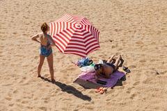 Os povos não identificados relaxam na praia da cidade nas costas Imagem de Stock
