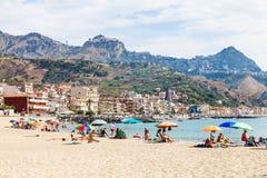 Os povos na areia encalham na cidade de Giardini Naxos Imagem de Stock