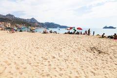 Os povos na areia urbana encalham na cidade de Giardini Naxos Imagens de Stock