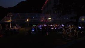 Os povos na noite sentam-se sob a tampa e comemoram-se video estoque