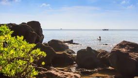 Os povos nadam no mar perto da tração dos barcos da praia da rocha perto vídeos de arquivo