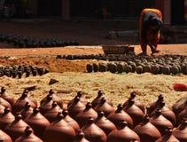 Os povos nepaleses s?o dando forma e de secagem acima a potenci?metros da cer?mica no quadrado da cer?mica imagem de stock royalty free