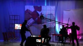 Os povos no estúdio da tevê do pavilhão Disparando em um programa televisivo silhuetas video estoque