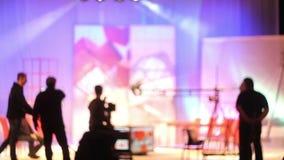 Os povos no estúdio da tevê do pavilhão Disparando em um programa televisivo silhuetas filme