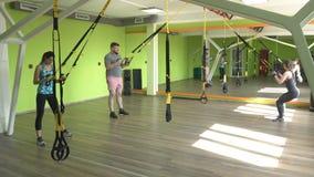 Os povos no gym são contratados nos laços de TRX e executam um exercício no tríceps, reforço da extensão do músculo vídeos de arquivo