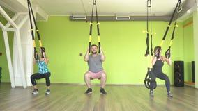 Os povos no gym são contratados nos laços e executam um exercício no tríceps, reforço da extensão do músculo filme