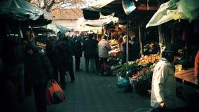 Os povos no mercado de rua estão procurando o alimento video estoque