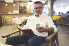 Os povos no trabalho usando o smartphone e na conexão sem fio ao Internet 4G no coffe compram Fotografia de Stock