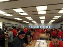 Os povos olham o relógio e os outros produtos na loja de Apple Imagem de Stock