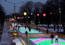 Os povos passam a noite na pista de patinagem colorida Fotos de Stock