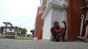 Os povos passam pelo ancião que implora pela esmola no pavimento da jarda da igreja video estoque