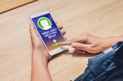 Os povos pedem a função do bot do bate-papo no app móvel procurando o cliente imagem de stock royalty free