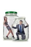 Os povos prendidos no frasco de vidro Imagens de Stock