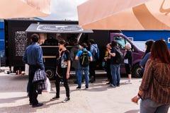 Os povos que esperam na linha para comprar puxaram sanduíches da carne de porco de um caminhão do alimento Fotos de Stock