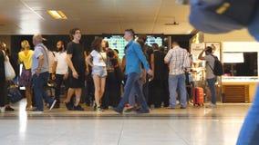 Os povos que olham a partida do calendário embarcam no aeroporto internacional Passageiros com bagagem que andam no terminal video estoque