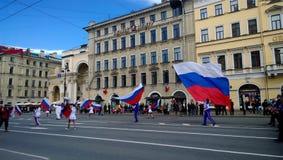 Os povos que participam em demonstrações do primeiro de maio em Nevsky Prospekt, levam grandes bandeiras nacionais da Rússia Fotografia de Stock