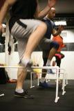 Os povos que saltam sobre obstáculos no gym imagens de stock