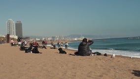 Os povos relaxam na praia de Barcelona no inverno e olham o mar tormentoso video estoque
