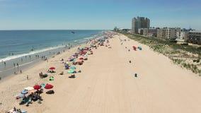 Os povos reunem-se à praia em um dia de grau de 90 sinais de adição na cidade Maryland do oceano vídeos de arquivo