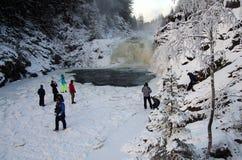 Os povos são fotografados na cachoeira Kivach do fundo no dia nebuloso de janeiro Carélia, Rússia Foto de Stock