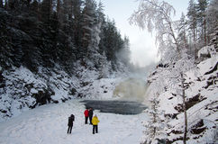 Os povos são fotografados na cachoeira Kivach do fundo no dia nebuloso de janeiro Carélia, Rússia Fotografia de Stock